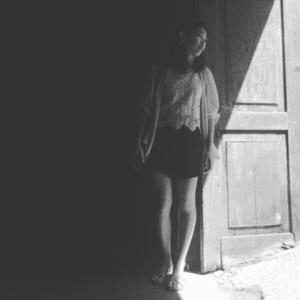 Young woman behind opened door